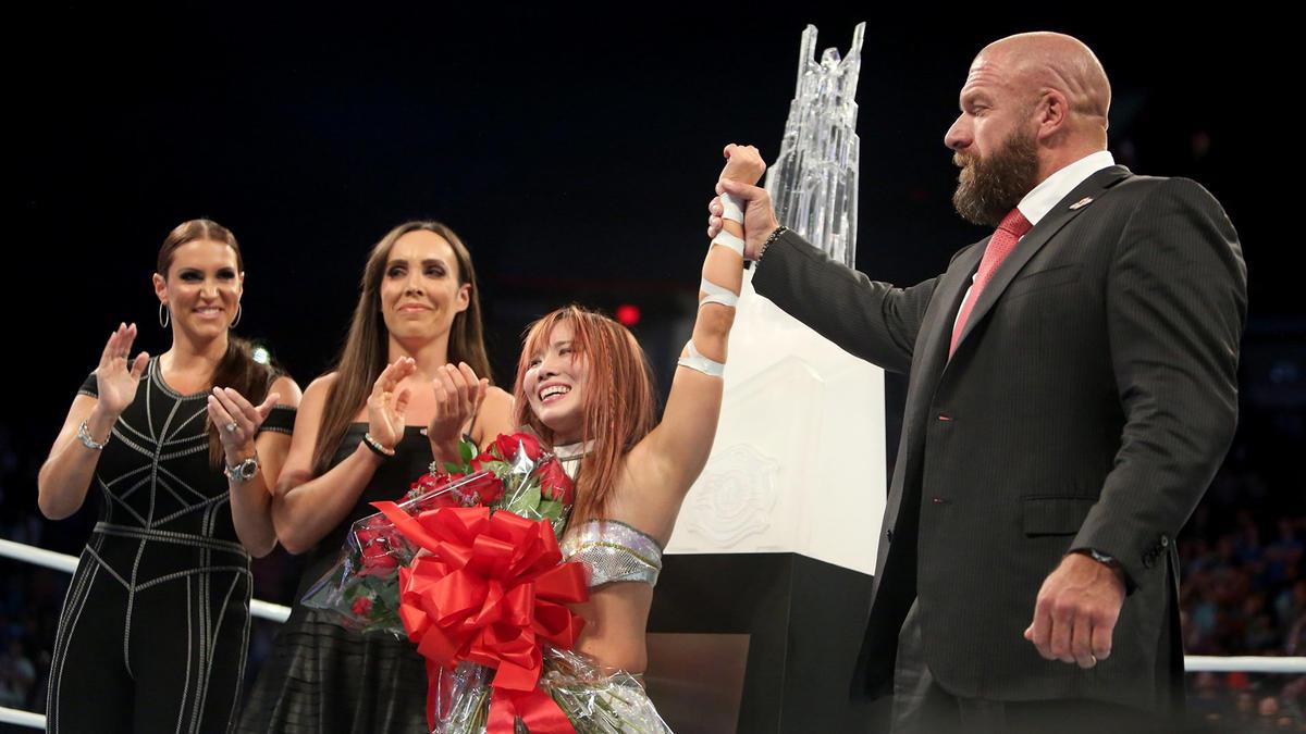 Le Directora de Marca de WWE Stephanie McMahon, la Directora Técnica de WWE Sara Amato y el COO Triple H presentan el trofeo.